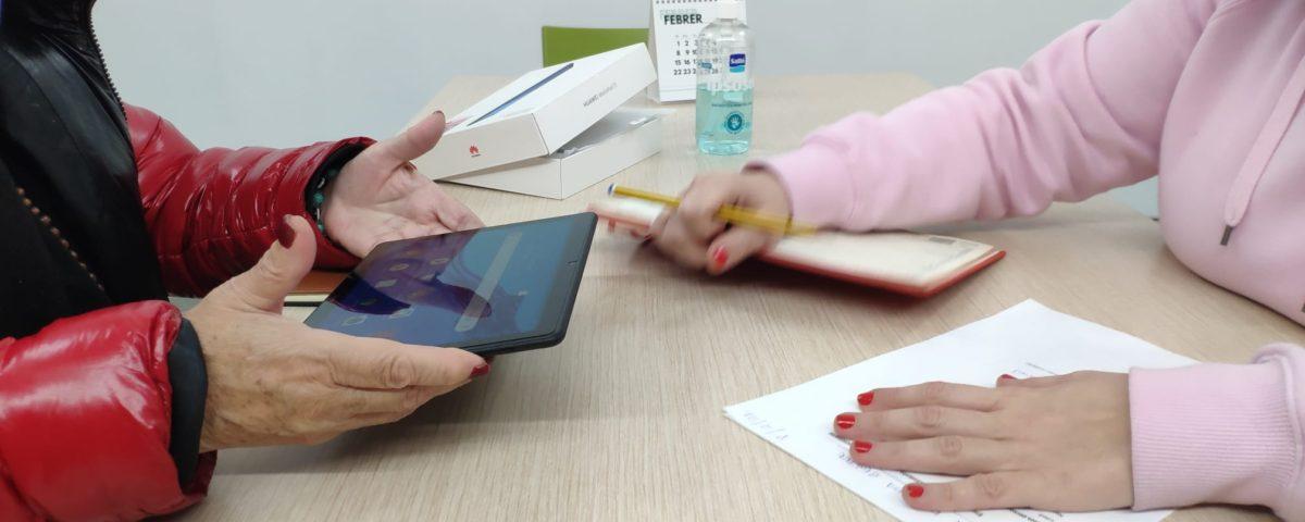 Una taula amb llibres, papers i una tablet. Unes mans utilitzant la tablet i unes altres agafant un boli