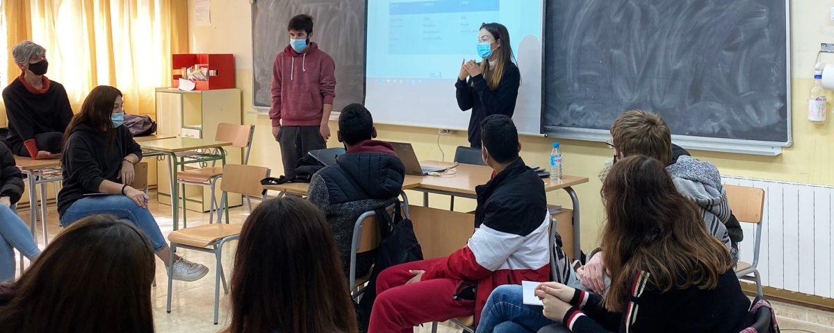 Veiem d'esquena a un grup de joves asseguts en una aula, davant seu, dues persones també joves explicant-los coses davant d'una pantalla de projecció.